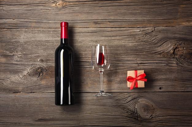ワイングラスと木製の背景上のギフトボックスとワインのボトル。あなたのテキストのためのコピースペースと平面図。