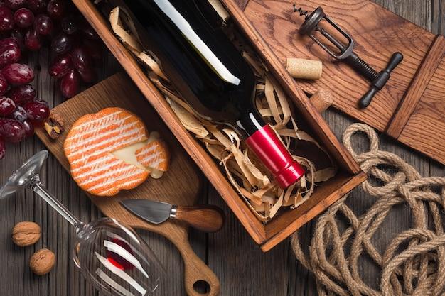 ガラス、コルク栓抜き、クリームチーズと木製の古いテーブルの上のボックスに赤ワイン。あなたの挨拶のためのスペースと平面図。