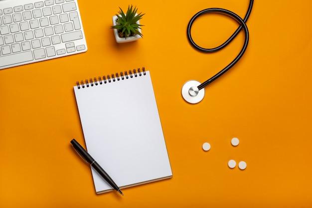 Вид сверху стола врача с блокнотом и ручкой стетоскопной клавиатуры