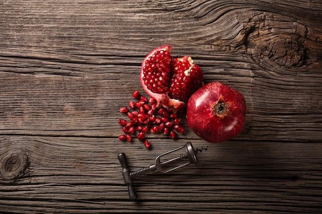 熟したザクロの果実と木製の背景にコルク抜き