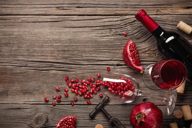 熟したザクロのフルーツ、ワイン、ボトル、木製の背景にコルク抜き