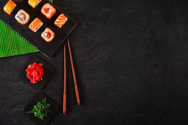 Суши набор сашими и роллы для суши подаются на каменном сланце