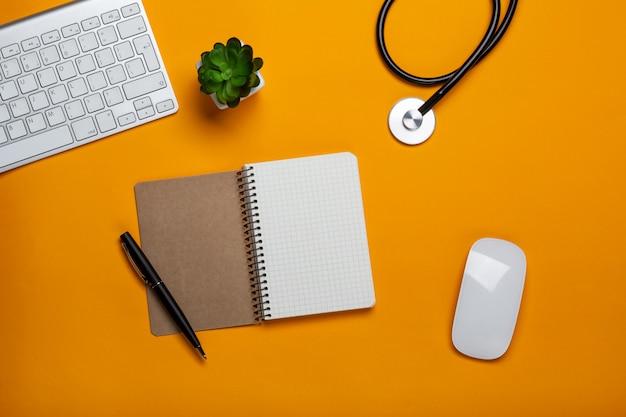 Вид сверху на стол врача с блокнотом и ручкой стетоскопной клавиатуры