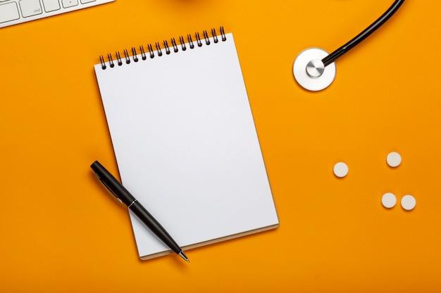 聴診器キーボードのメモ帳とペン、処方薬と薬と医者の机の上から見る