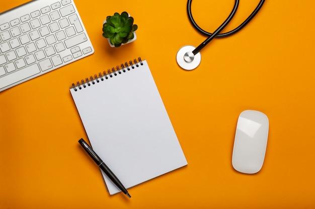 聴診器キーボードのメモ帳とペンを持つ医師のテーブルの上から見る