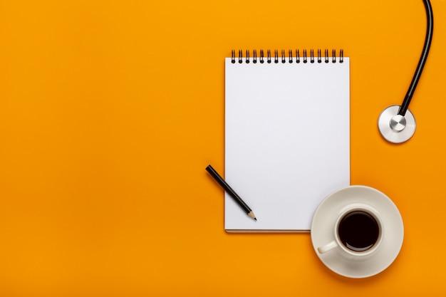 ペンでクリップボードに聴診器、コーヒー、空白の紙をドクターデスクテーブルの上から見る。