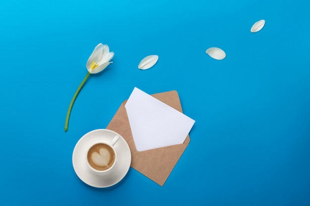 花びら、一杯のコーヒー、愛のメモと青い背景上の封筒の白いチューリップ