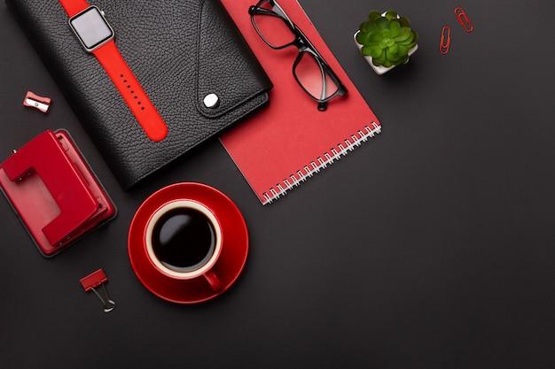 赤いコーヒーカップ、メモ帳、目覚まし時計、トップビューで花と黒の背景