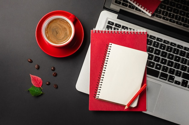 黒いテーブルの上のノートパソコンとコーヒーカップの上の空白のメモ帳