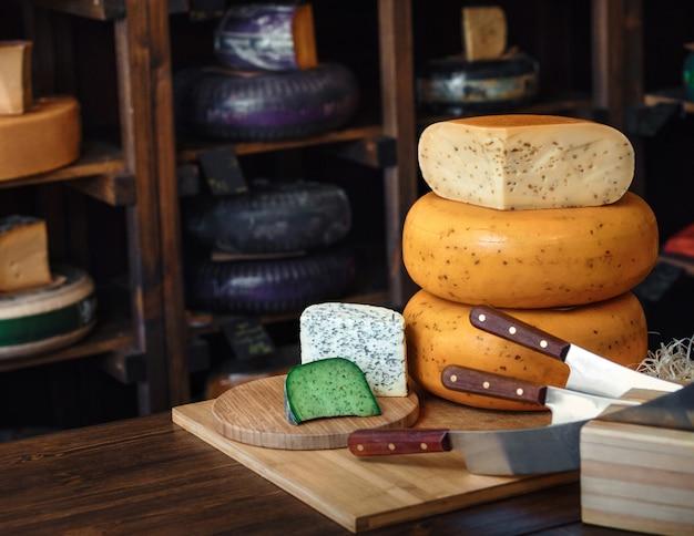 ナイフでテーブルの上の金型とおいしいチーズブルーグリーンバイオレットチーズの様々な種類の木の板