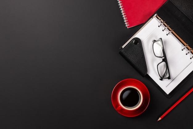 一杯のコーヒーとノートとオフィスデスクテーブル。コピースペース平面図