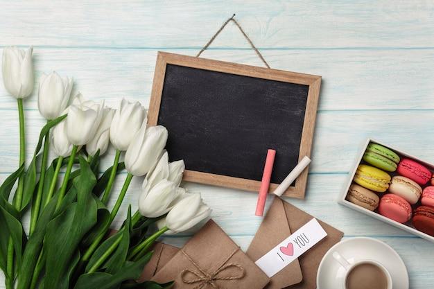 チョークボード、一杯のコーヒー、愛のメモと青い木の板にマカロンの白いチューリップの花束