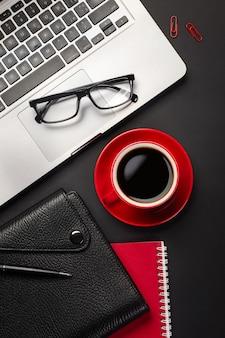 空白の画面のラップトップコンピューター、ノートブック、マウス、一杯のコーヒー、その他のオフィスの黒いオフィスデスクテーブル。