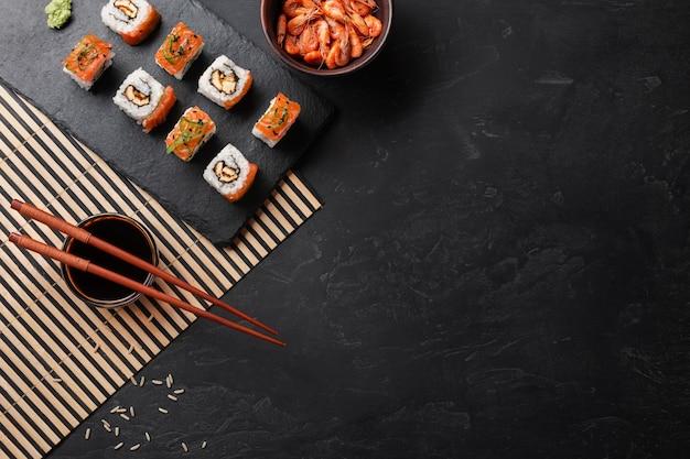 Набор суши и маки на каменный стол. вид сверху с копией пространства
