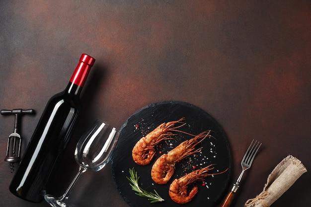 ハート型のエビと茶色の背景にワインのロマンチックなディナー。コピースペース平面図