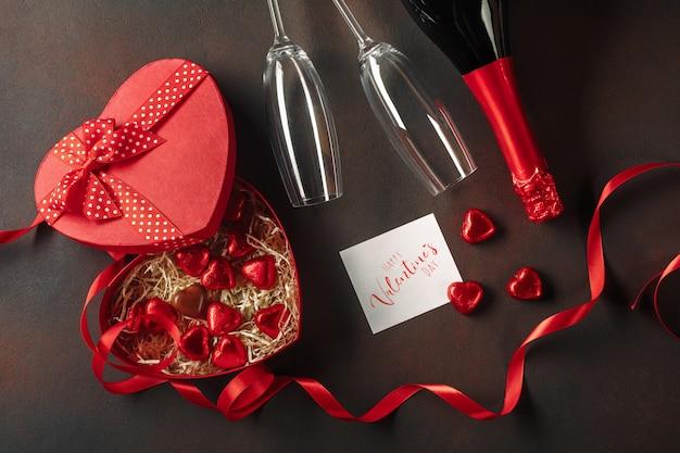 День святого валентина с коробкой конфет в форме сердца с бутылкой шампанского с бокалами и запиской