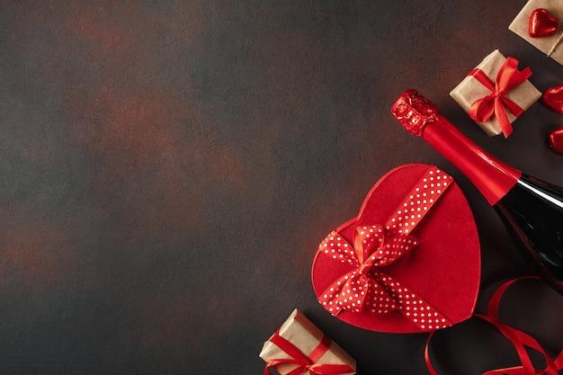 心からの贈り物とスパークリングワインの形のチョコレートの箱とバレンタインデー。コピースペース平面図。