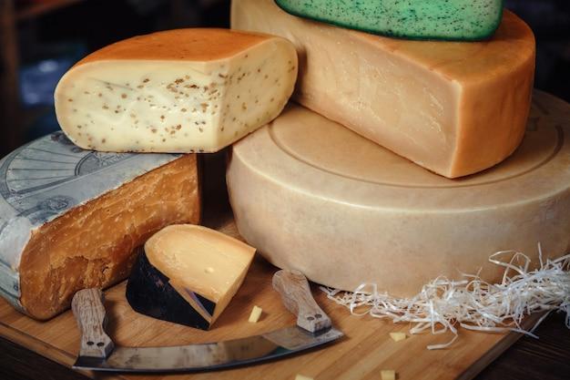 さまざまな種類のおいしいナイフグリーンテーブルバンカーチーズとテーブルの上の木の板