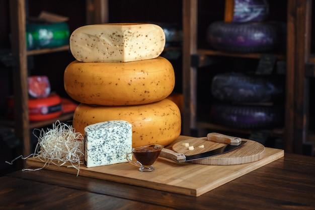 さまざまな種類の美味しいブルーグリーンバイオレットチーズと成形チーズのテーブルの上の木の板
