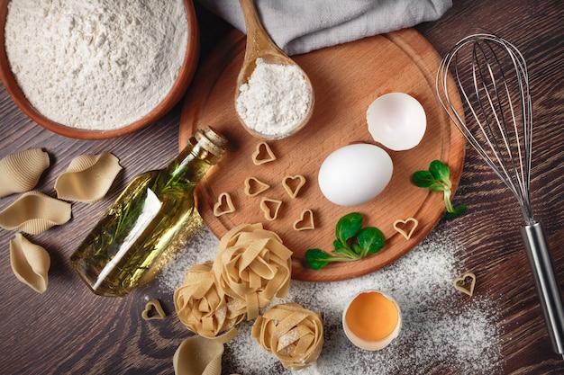 Пекарские ингредиенты. мука с сырым яйцом, масло для теста, макароны на деревянной доске