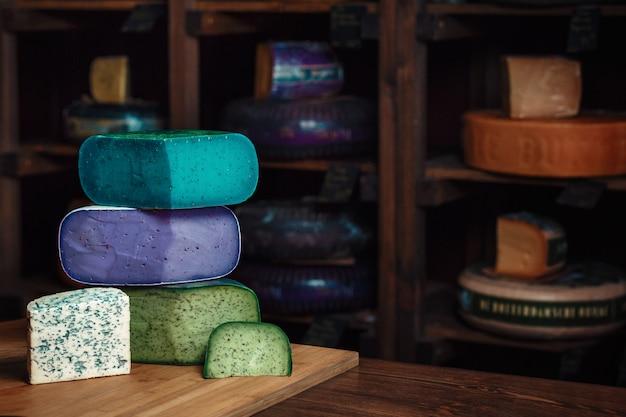 テーブルの上の金型とおいしいチーズブルーグリーンバイオレットチーズの様々な種類の木の板