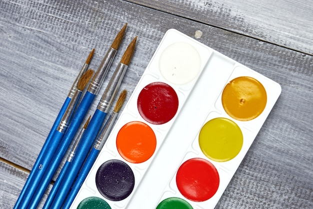 Палитра акварельных красок и кисточек разных размеров, лежащих на сером дереве
