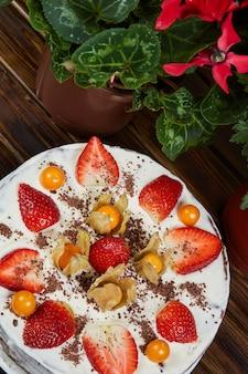 イチゴとサイサリスの木製の背景に誕生日ケーキ