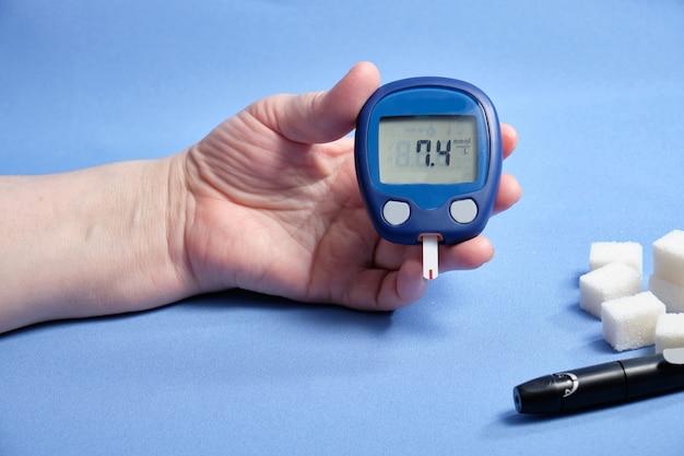 Женщина делает анализ крови на сахар, на синем пространстве. место для текста