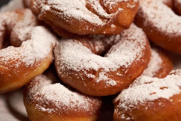 白いプレートに粉砂糖を振りかけたドーナツ