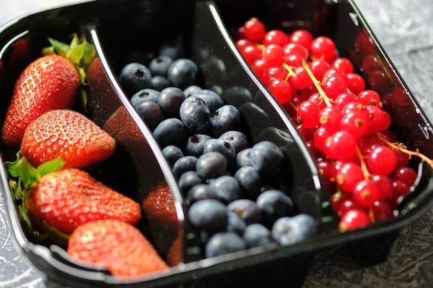 Пластиковая тара коробка с ягодами, красной смородиной, ежевикой и клубникой на сером фоне