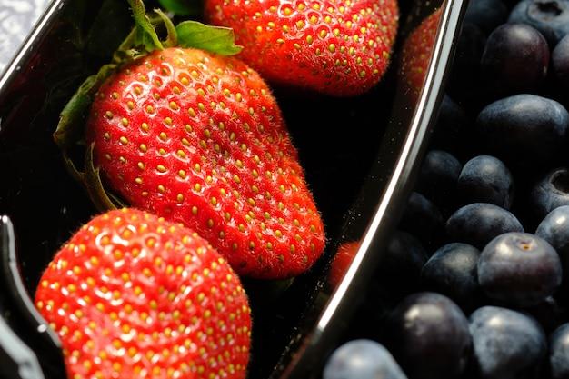 Пластиковые контейнеры, коробка с ягодами, красной смородиной, черникой и клубникой. закрыть