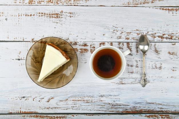 軽い木製のコーヒーとチーズケーキ。喫茶店でのコーヒー、コピー。軽いコンクリートのニューヨークチーズケーキ、トップビュー。古典的なチーズケーキと一杯のコーヒー。