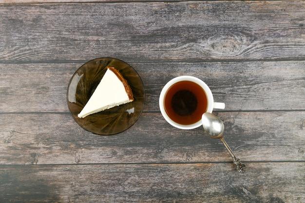 暗い木製のコーヒーとチーズケーキ。 。茶色の木の横にあるチーズケーキ。レトロなカップ。喫茶店でのコーヒー、コピー。