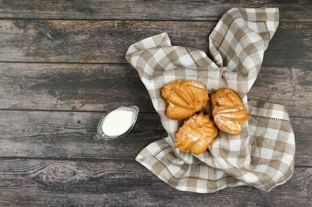 ダークウッドの牛乳とシューケーキ。市松模様のタオルでバスケットに。 。カッテージチーズとシック。木製の籐のボウルに小さなカスタードケーキ