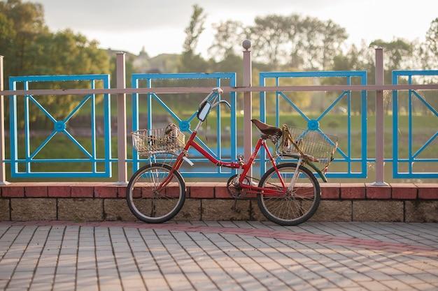 バスケットと古い赤い自転車は日没でフェンスの上に立つ