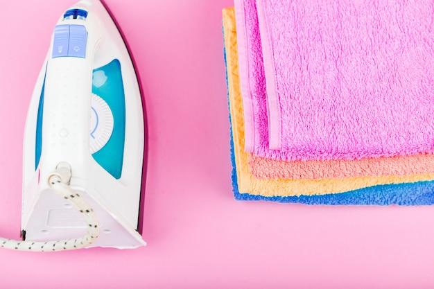 Концепция глажения одежды. домашний заказ. гладильная и гладильная ткань. электрический утюг на розовом пространстве с полотенцами. разноцветные полотенца.
