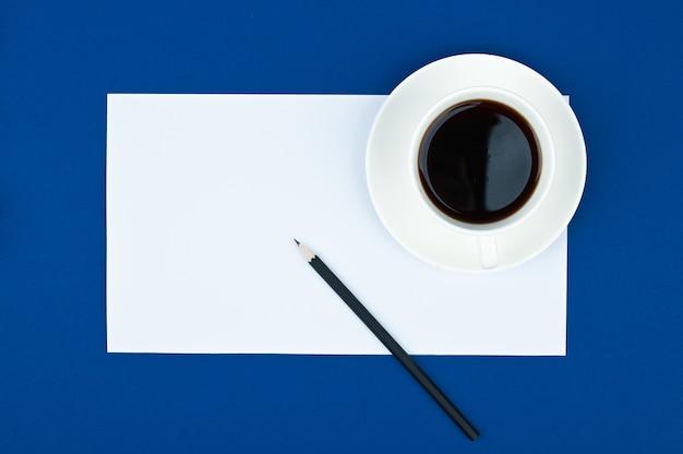 メモ帳、鉛筆、コーヒーカップのオフィスデスクテーブル。コピースペースの平面図