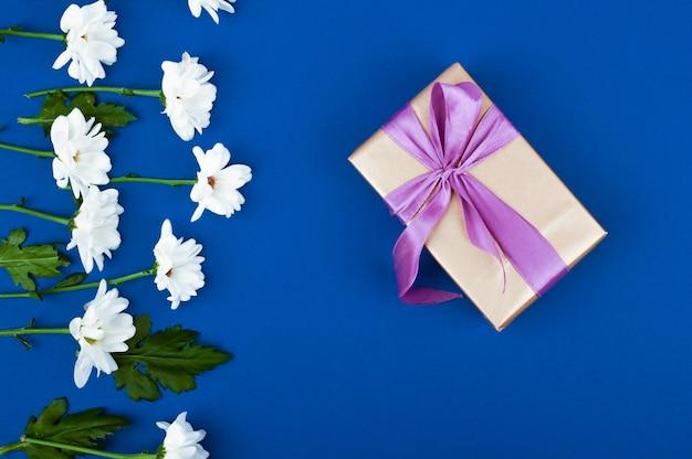 Подарочная коробка и цветы на синем столе. открытка на день рождения, женщины или день матери. вид сверху
