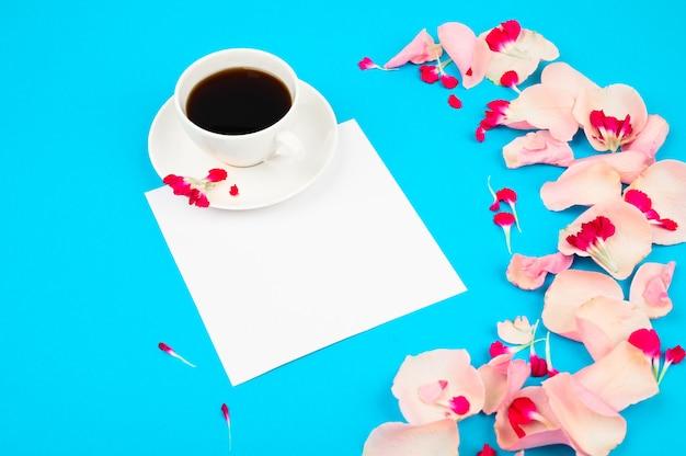 Чашка кофе с цветами декора на светло синий стол. концепция любви и романтики.