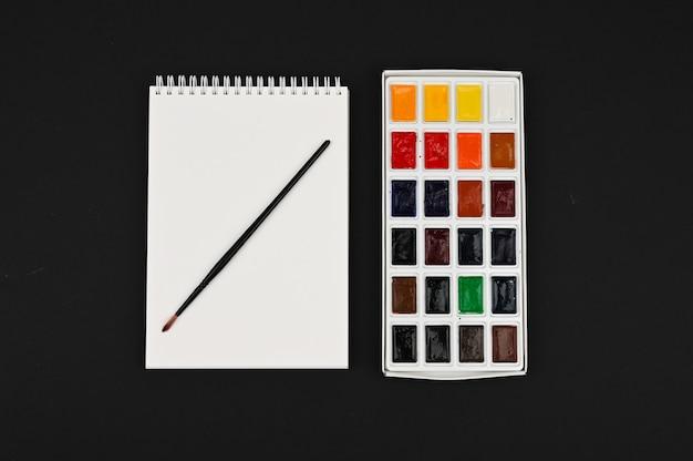 Набор для рисования. белый лист бумаги, акварель и кисти. вид сверху