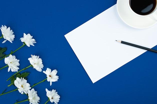 女性のワークスペース。青い空間にコーヒーと花のフレームのカップ。コピースペース