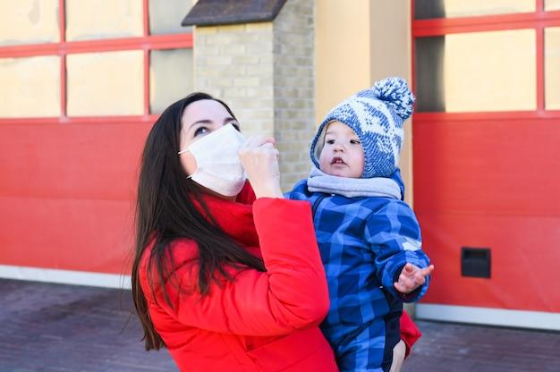 Молодая женщина в маске и держит в руках маленького мальчика. защитные меры. мать и дитя в карантине.