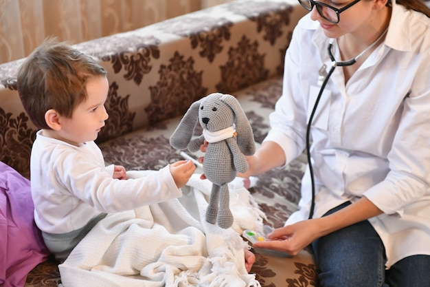 子供が医者と一緒におもちゃに薬を与える