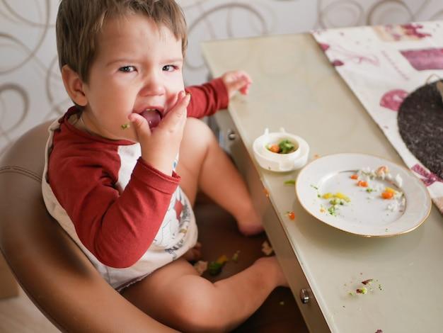テーブルにいる子供は野菜を食べます。子供の頃、食べ物、人のコンセプト-夕食に健康的な朝食を食べる小さな子供