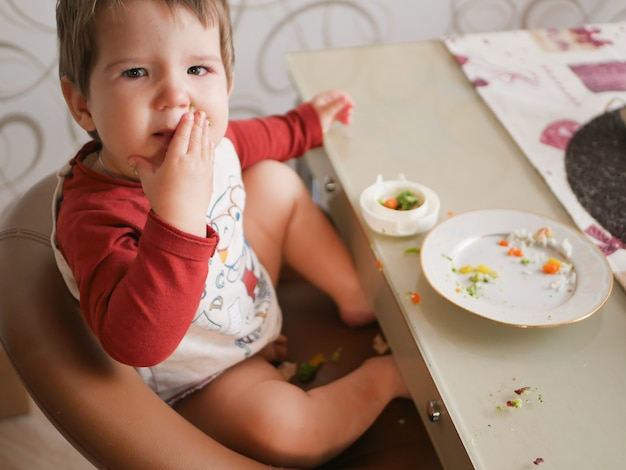 Ребенок за столом ест овощи. детство, еда и люди концепции - маленький ребенок ест здоровый завтрак на ужин