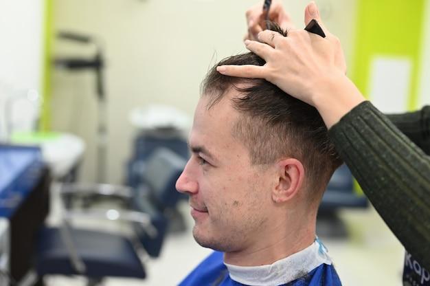 若い男は美容院で髪を切った。美容院で散髪。理髪店