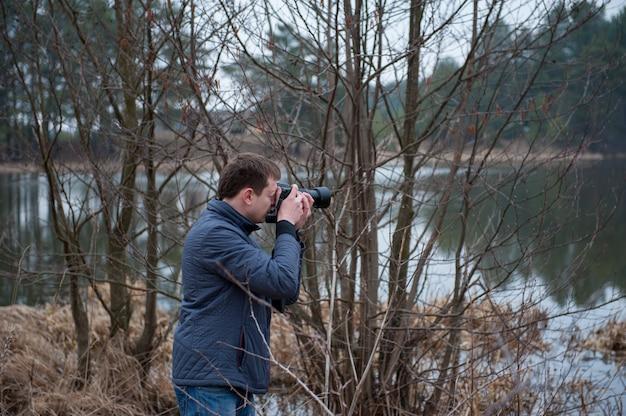 Фотограф снимает пейзаж, пасмурное фото природы, фотограф за работой