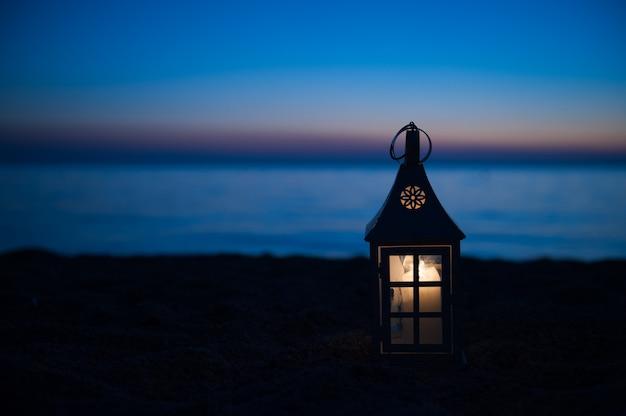 ビーチの近くで燃えているランタン、日没の照明。夕暮れ時のビーチの近くの木製デッキのランタン。