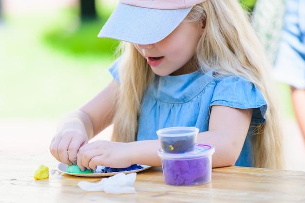 Детское рукоделие. глина лепка. маленькая девочка занимается рукоделием