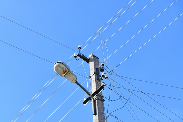 曇りの青い空を背景にランプポストで有線電気の伝送のための古いコンクリート電柱。私を時代遅れにしました。電気の供給方法